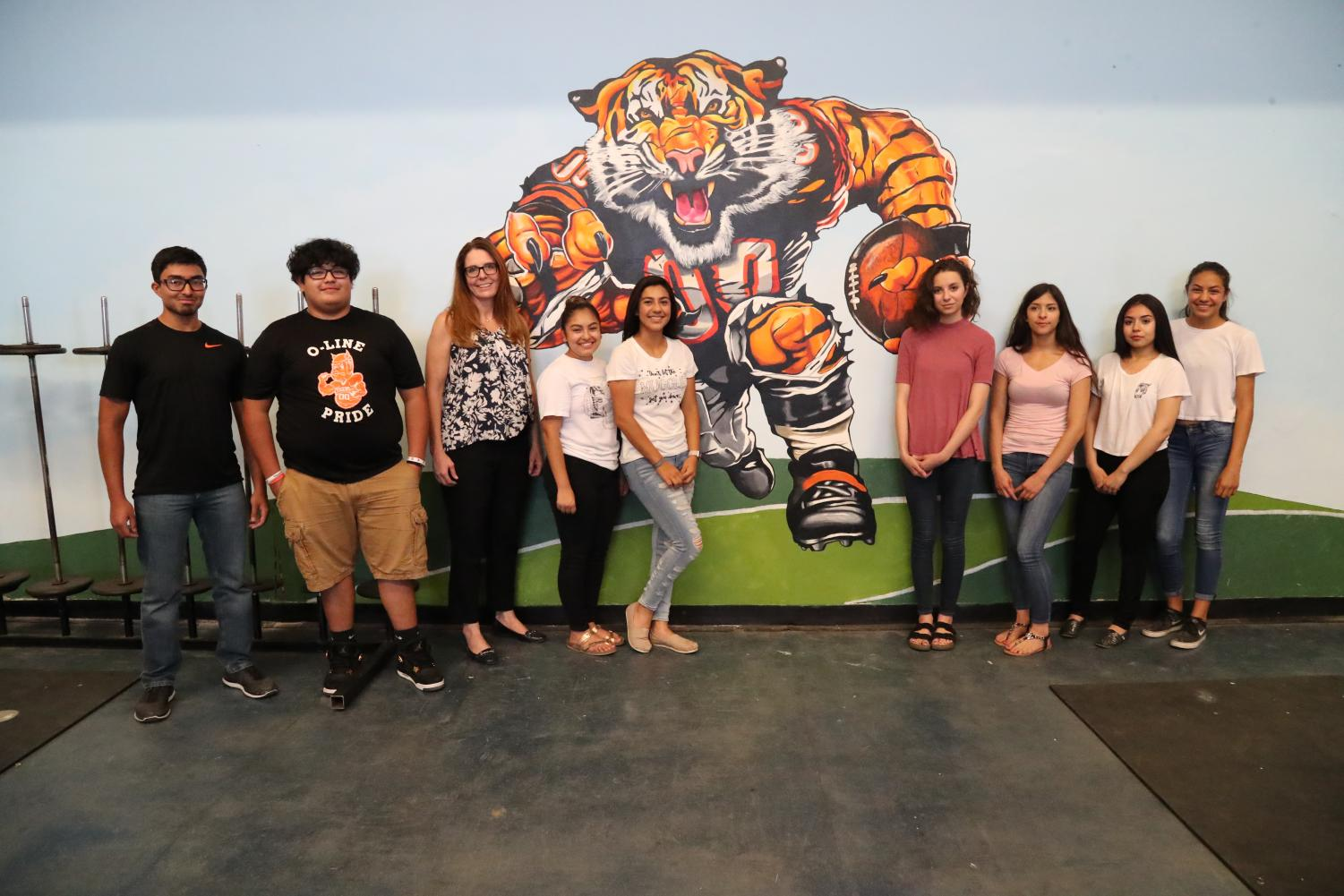 Mrs. Garrison and students reveal their mural inside the school's weight room.