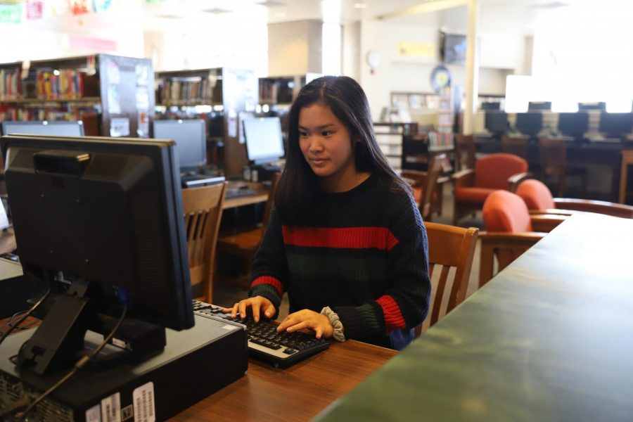 Senior, Grace Zhao, uses the librarys online catalog for research.